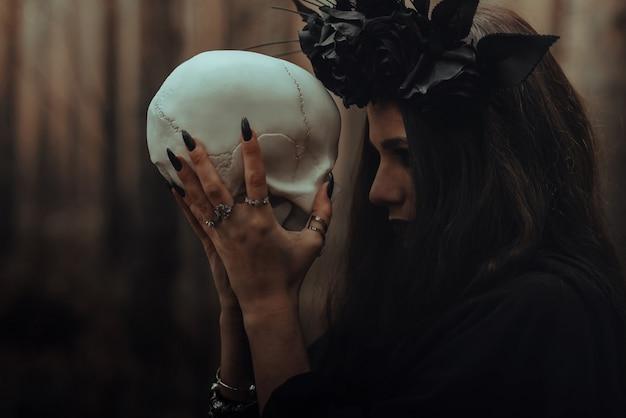 Portret van een verschrikkelijke heks met een schedel in de handen van een dode man voert een occult mystiek ritueel uit in het bos