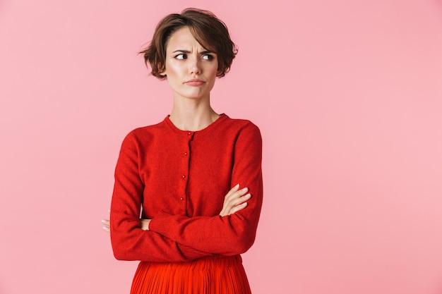 Portret van een verstoorde mooie jonge vrouw die rode kleren draagt die zich geïsoleerd over roze achtergrond bevinden