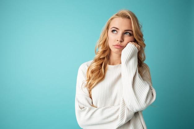 Portret van een verveeld jong blondemeisje dat weg kijkt