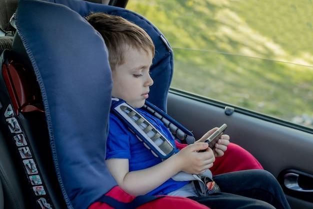 Portret van een verveeld jongetje in een autostoeltje. veiligheid van het vervoer van kinderen