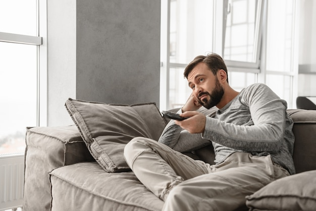 Portret van een verveelde afstandsbediening van tv van de jonge mensenholding
