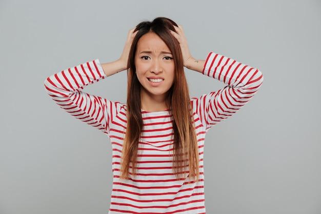 Portret van een verward aziatisch meisje staan