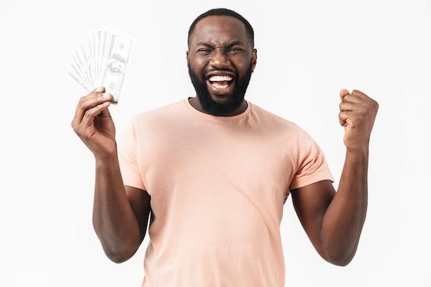 Portret van een verwarde afrikaanse man met een shirt dat geïsoleerd staat en geldbankbiljetten toont