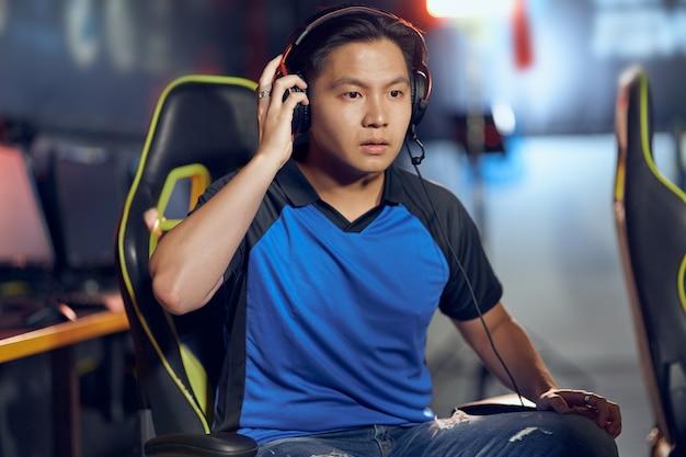 Portret van een verwarde aziatische mannelijke cybersport-gamer die een koptelefoon draagt en naar het pc-scherm kijkt