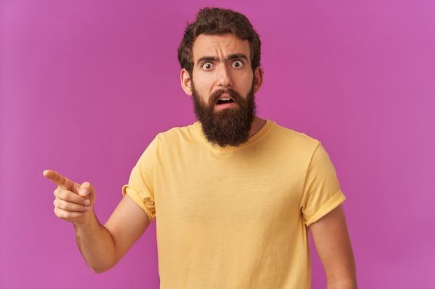 Portret van een verwarde, bebaarde jongeman met bruine ogen die een geel t-shirt draagt, wijst naar links, verbaasd staan