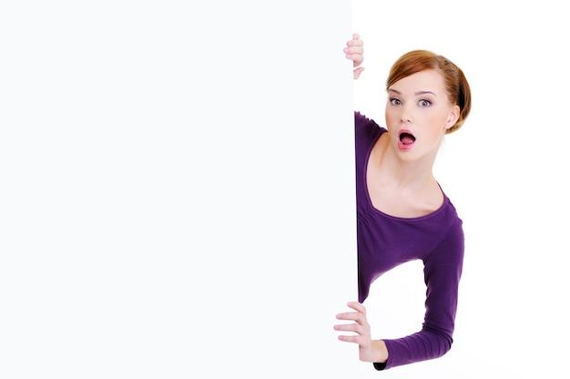Portret van een verwarde blik van een vrouw kijkt uit vanwege een leeg reclamebord
