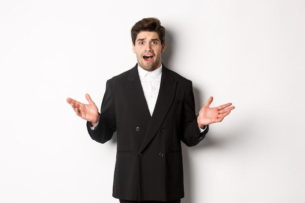 Portret van een verwarde en bezorgde knappe man in pak, kijkend naar iets vreemds, handen zijwaarts gespreid en verbaasd tegen een witte achtergrond.