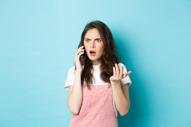 Portret van een verwarde en geschokte vrouw ontvangt slecht nieuws terwijl ze op een smartphone praat, ontvangt een slecht telefoontje, staande tegen een blauwe achtergrond.