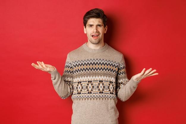 Portret van een verwarde en teleurgestelde knappe jongen, klaagt over kerstmis, spreidt handen zijwaarts en fronst ontevreden, staande in kersttrui over rode achtergrond