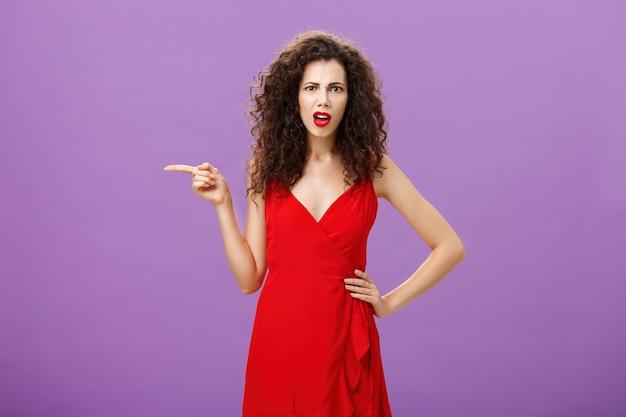 Portret van een verwarde en verwarde aantrekkelijke vrouw met krullend haar in een rode elegante jurk die perplex staat...