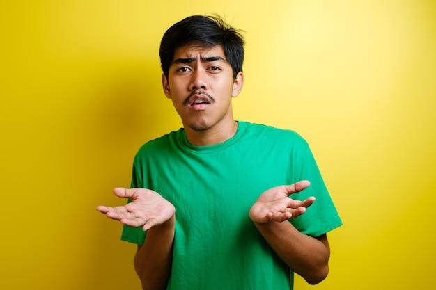 Portret van een verwarde geërgerde man die zijn schouders ophaalt, zijn armen opheft, vraagt en geen idee heeft wat er gebeurt. tegen gele achtergrond