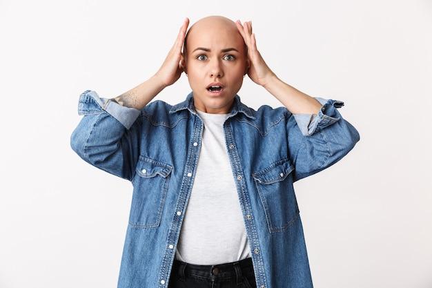 Portret van een verwarde gefrustreerde mooie jonge haarloze vrouw die vrijetijdskleding draagt die geïsoleerd staat