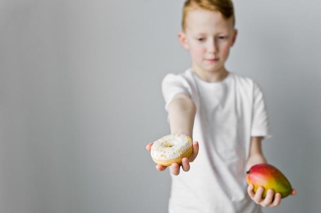 Portret van een verwarde jong geitjejongen die tussen doughnut en mango over grijze achtergrond kiest
