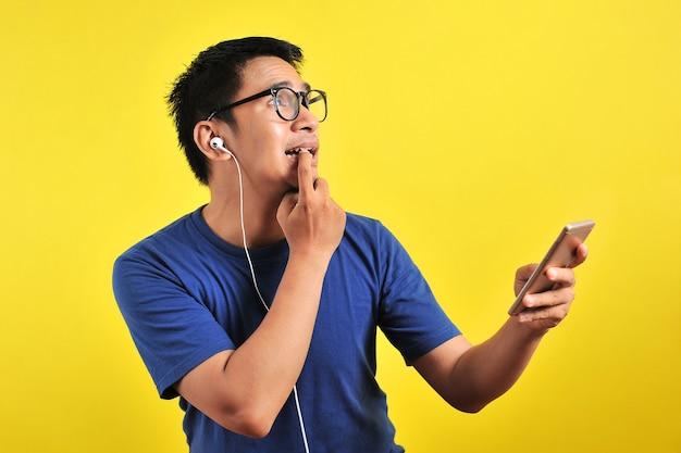 Portret van een verwarde jonge aziatische man die in zijn vinger bijt en live muziek luistert van smartphone met headset, geïsoleerd op gele achtergrond