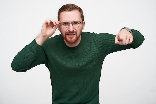 Portret van een verwarde jonge, bebaarde man met een kort kapsel die zijn bril vasthoudt terwijl hij verbaasd kijkt, vooruitstekend met index figer terwijl hij staat