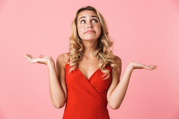 Portret van een verwarde jonge mooie blonde schattige vrouw in jurk poseren geïsoleerd over roze muur met copyspace