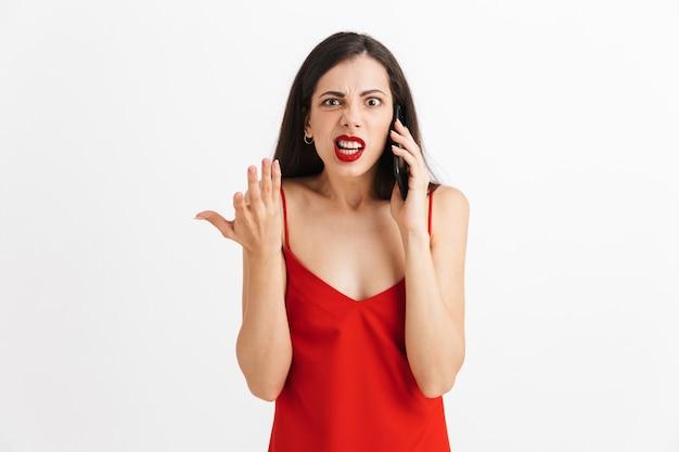 Portret van een verwarde jonge vrouw in geïsoleerde jurk, praten over de mobiele telefoon
