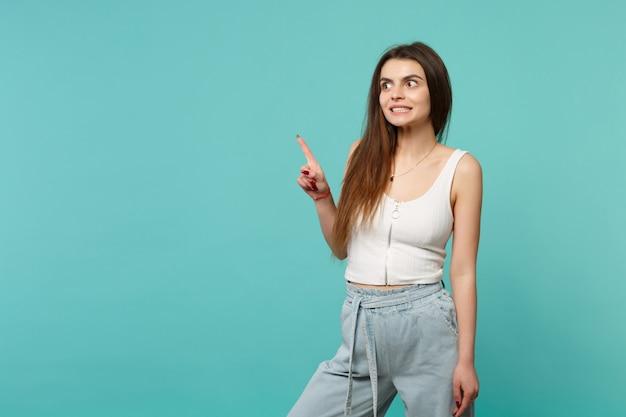 Portret van een verwarde jonge vrouw in lichte vrijetijdskleding die wijzende wijsvinger opzij kijkt geïsoleerd op een blauwe turquoise muurachtergrond. mensen oprechte emoties, lifestyle concept. bespotten kopie ruimte.