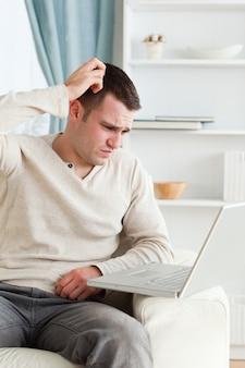Portret van een verwarde man met behulp van een laptop