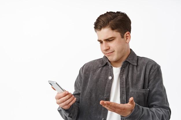 Portret van een verwarde man staart naar het scherm van de smartphone en haalt zijn schouders op, kan het bericht niet begrijpen, kijkt naar de melding van een mobiele telefoon besluiteloos, staat op wit