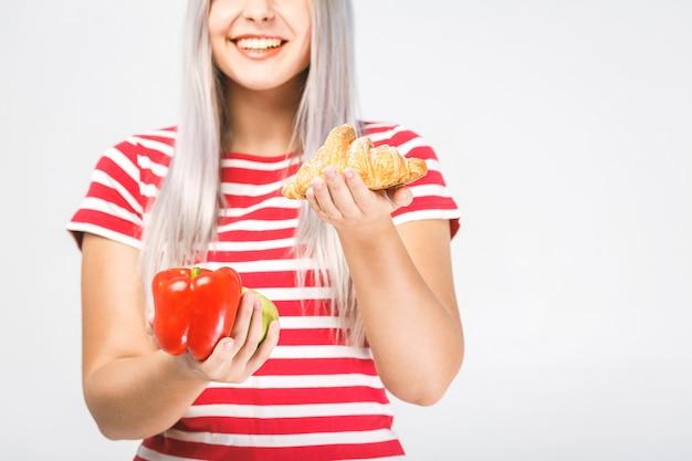 Portret van een verwarde mooie jonge blonde vrouw die tussen gezond en ongezond voedsel kiest. geïsoleerd op witte achtergrond. detailopname.