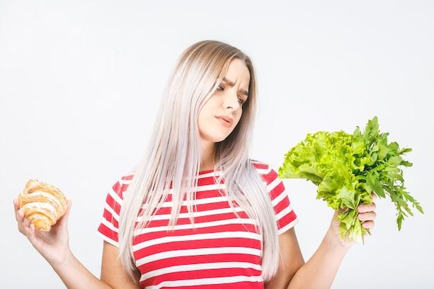 Portret van een verwarde mooie jonge blonde vrouw die tussen gezond en ongezond voedsel kiest. geïsoleerd op witte achtergrond.