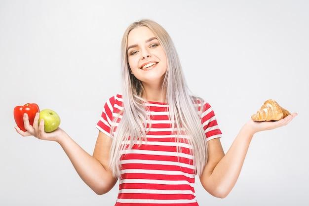 Portret van een verwarde mooie jonge blonde vrouw die tussen gezond en ongezond voedsel kiest