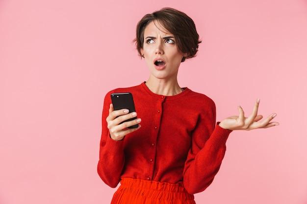 Portret van een verwarde mooie jonge vrouw die rode kleren draagt die zich geïsoleerd bevinden