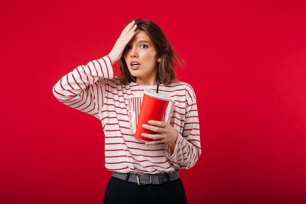 Portret van een verwarde popcorn van de vrouwenholding