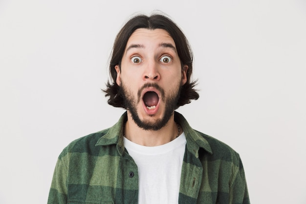 Portret van een verwarde, verraste jonge, bebaarde brunette man met een geruit hemd dat geïsoleerd over een witte muur staat