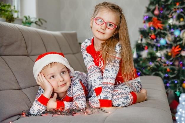 Portret van een vierjarige tweelingbroer en zus in pyjama's thuis op de bank met kerstboom