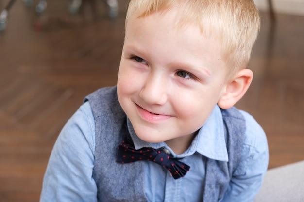 Portret van een vijfjarige blonde jongen in een overhemd, vest en vlinderdas
