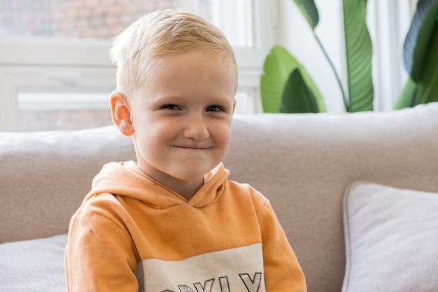 Portret van een vijfjarige blonde jongen in een sweatshirt