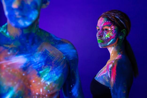 Portret van een vlezige man en vrouw geschilderd in ultraviolet poeder. body art gloeit in ultraviolet licht
