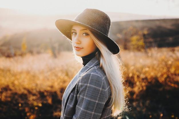 Portret van een volwassen aantrekkelijke dame gekleed in pak en het dragen van hoed kijken camera glimlachen tegen geweldige zonsondergang tijdens het wandelen buiten.