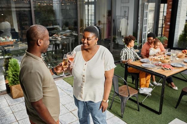 Portret van een volwassen afro-amerikaans koppel dat geniet van een drankje op het buitenterras tijdens een familiebijeenkomst...