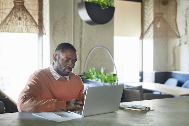 Portret van een volwassen afro-amerikaanse man die een laptop gebruikt terwijl hij in een modern café-interieur werkt, versierd met verse groene planten, kopieer ruimte