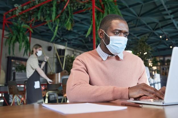 Portret van een volwassen afro-amerikaanse man die een masker draagt tijdens het gebruik van een laptop in een modern café-interieur, kopieer ruimte