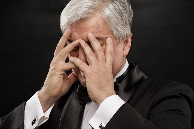 Portret van een volwassen bedrijfsmens die gedeprimeerd van het werk over zwarte achtergrond kijkt