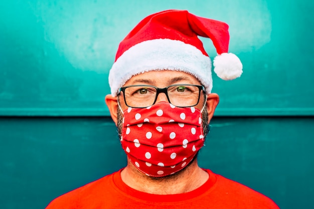 Portret van een volwassen blanke man met een rood beschermingsmasker voor coronavirus vocid-19 en kerstman chrismtas-hoed