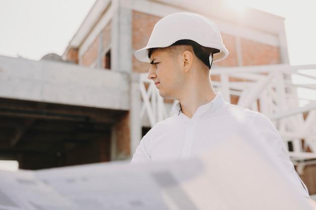 Portret van een volwassen eigenaar die het werk in zijn gebouw inspecteert met een plan in zijn handen.