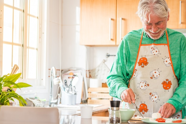 Portret van een volwassen en oude man die thuis in de keuken lacht. senior bereiden van voedsel om alleen binnen te lunchen. gepensioneerde mannelijke lerende kok
