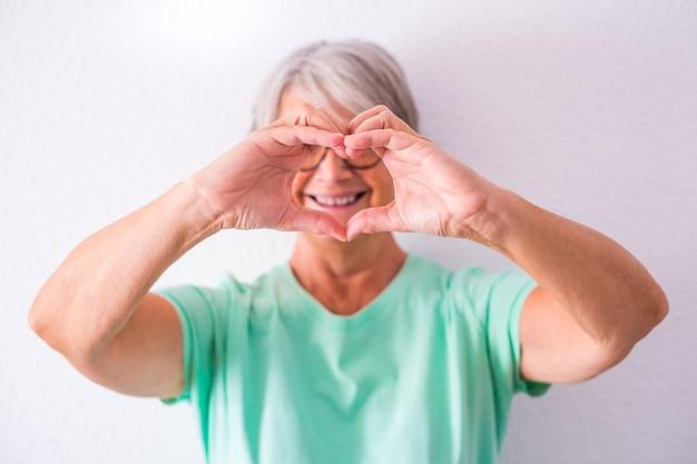 Portret van een volwassen en oude vrouw die hun camera een hart laat zien, gemaakt met haar handen die glimlachen en plezier hebben thuis. vrouwelijke senior die voor mensen zorgt en van mensen houdt