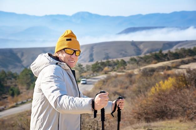Portret van een volwassen glimlachende man met nordic walking-stokken die hoog in de bergen staan.