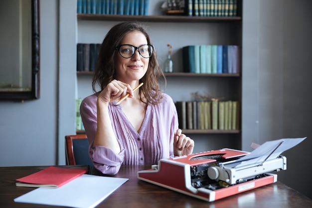 Portret van een volwassen lachende authoress zitten aan de balie