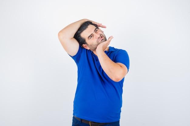 Portret van een volwassen man die zich uitstrekt nek in blauw t-shirt en op zoek ontspannen vooraanzicht