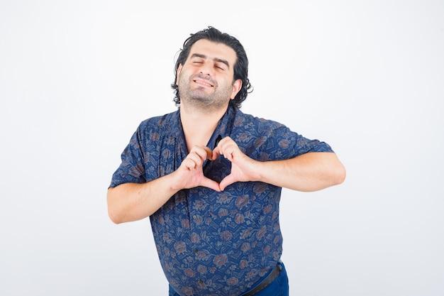 Portret van een volwassen man hart gebaar in shirt tonen en vredig vooraanzicht kijken