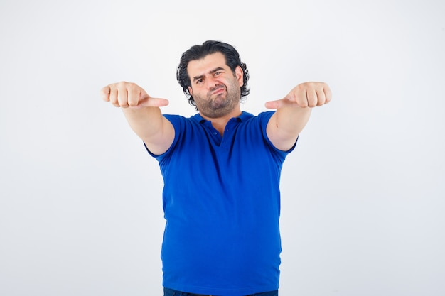 Portret van een volwassen man met middelste duimen in blauw t-shirt en besluiteloos vooraanzicht op zoek