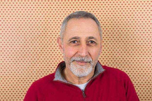 Portret van een volwassen man tegen hartvormbehang