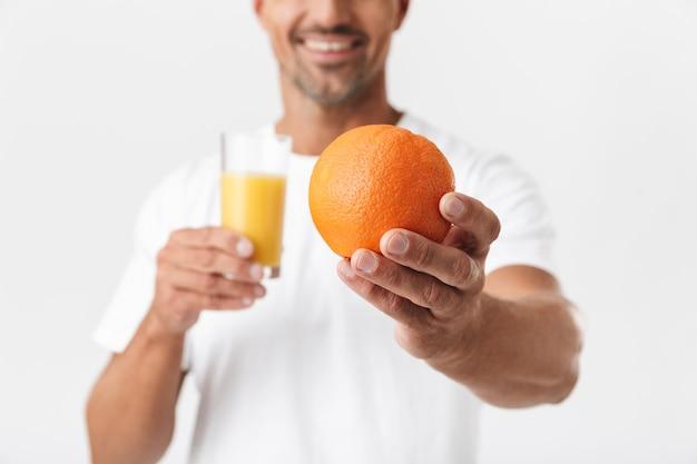 Portret van een volwassen man van 30 met borstelharen die een casual t-shirt draagt met een glas sap en sinaasappelfruit op wit wordt geïsoleerd